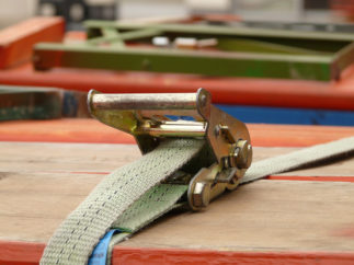 A ratchet securing a rope around planks of wood