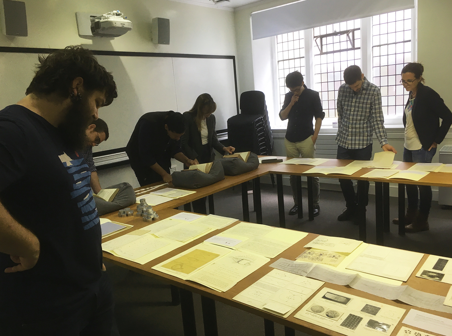 Workshop attendees looking at archive material displayed on tables